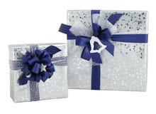 Setu dwa prezenta pudełka srebra opakunku błękitnego faborku błyszczący papierowy łęk odizolowywający Obrazy Royalty Free