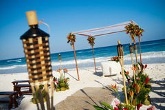 Setup for beach wedding. A view of tiki torches or oil lamps and setup for a tropical beach wedding stock photography
