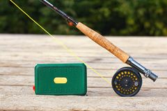 Fly fishing rod setup. Setup of a fly fishing rod with tied fly lure and lure box stock image