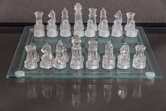 Setup of the start of chess game on a glass chessboard Stock Images