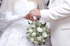 Setzen auf einen Hochzeitsring Stockbild