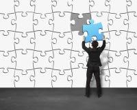 Setzen des einzigartigen blauen Puzzlespiels in Wand Lizenzfreie Stockfotos