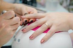 Setzen des Lacks auf Nägel Verarbeitung von Nägeln im Kosmetiksalon Lizenzfreie Stockfotografie