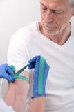 Setzen einer Aderpresse auf den Arm eines Patienten Stockfotografie