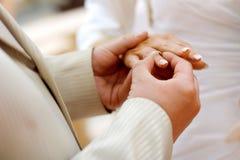 Setzen eines Hochzeitsringes auf Finger der Braut Lizenzfreie Stockfotografie