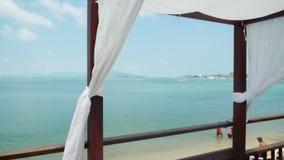 Setzen Sie Überdachungen mit Sonnenruhesesseln auf Seeansicht am sonnigen Tag auf den Strand Luxusstrandzelte, Gazebo an einem Er stock footage