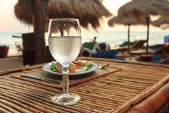 Setzen Sie Abend auf dem Sonnenuntergang mit Glas des Wassers und des Abendessens auf den Strand Stockbilder