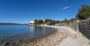 Setzen Sie am altem dominikanischem Kloster und an Zlatni-Ratte im Hintergrund, Bol, Insel von Brac, Kroatien auf den Strand Lizenzfreies Stockfoto