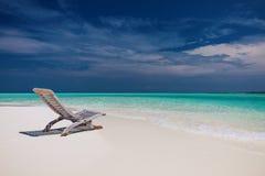 Setzen Sie Ansicht des erstaunlichen Wassers in Malediven - leerer Stuhl auf den Strand Lizenzfreies Stockfoto