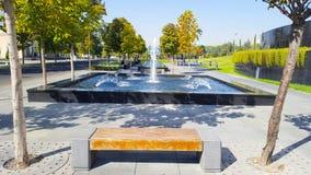 setzen Sie auf dem Hintergrund des Brunnens auf die Bank, der durch Bäume im Herbst umgeben wird Stockbild