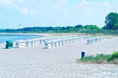Setzen Sie auf der deutschen Ostsee mit Strandstuhl und Feiertagsgefühl mit Sand auf den Strand lizenzfreies stockfoto