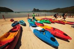 Setzen Sie auf Phi Phi Island mit vielen bunten Booten und Männern mit Rucksäcken auf den Strand Lizenzfreies Stockfoto