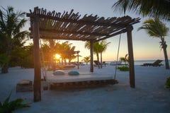 Setzen Sie Betten unter Palmen an perfektem tropischem auf den Strand Lizenzfreie Stockfotografie