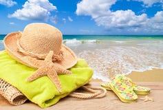 Setzen Sie Beutel mit Sun-Hut auf den Strand Stockbilder