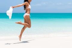 Setzen Sie Bikinikörper - sexy dünnes Beinfrauenspringen auf den Strand stockfotos