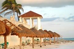 Setzen Sie blauen Ozean und Regenschirme 3 der grünen Stühle auf den Strand Lizenzfreie Stockfotos