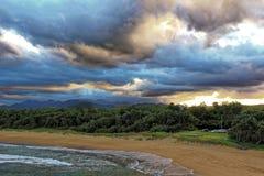 Setzen Sie Bucht mit Ansichten zum Hügelland durch bewölkten Himmel auf den Strand Stockbild