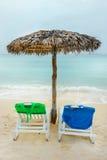 Setzen Sie charis und eine Strohhütte auf dem kubanischen Strand auf den Strand Stockfotografie