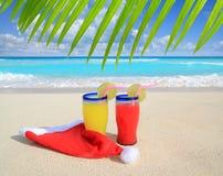 Setzen Sie Cocktails mit Sankt-Weihnachtshut auf den Strand Stockfoto
