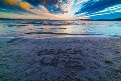 Setzen Sie das Leben auf den Strand, das auf den Sand bei Sonnenuntergang geschrieben wird lizenzfreie stockfotografie