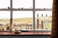Setzen Sie Dekorationen wie Oberteile und verwittertes Glas auf einem Fenster auf den Strand Stockfotografie