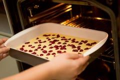 Setzen Sie den Kuchen in den Ofen, Kirschschwammkuchen ein lizenzfreies stockbild