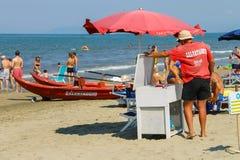 Setzen Sie den Leibwächter auf den Strand, der indem Sie Leute in Viareggio, Italien umgeben wird, stillstehen Stockbild