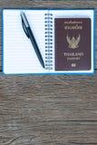 Setzen Sie den Stift und den Thailand-Pass auf eine Leerseite eines noteboo Lizenzfreies Stockfoto