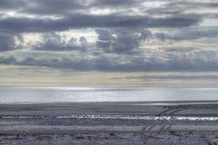 Setzen Sie an der Dämmerung mit Gummireifenspuren im Sand auf den Strand Stockfotografie