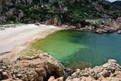 Setzen Sie an der felsigen Küstenlinie in Sardinien, Italien auf den Strand Stockfoto