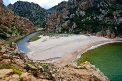 Setzen Sie an der felsigen Küstenlinie in Sardinien, Italien auf den Strand Stockfotografie
