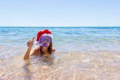 Setzen Sie die Ferienspaßfrau auf den strand, die ein Maskenrohr und einen Weihnachtshut für das Schwimmen im Ozeanwasser trägt N lizenzfreies stockbild