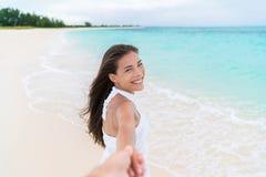 Setzen Sie die Frau auf den Strand, die den Freund betrachtet, der Hand auf Flitterwochenferien hält stockbilder