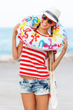 Setzen Sie die Frau auf den Strand, die glücklich sind und bunte tragende Sonnenbrille und den Strandhut, der Sommerspaß während  Stockfoto