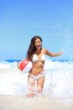 Setzen Sie die Frau auf den Strand, die mit dem Ball spielt, der das Spaßspritzen hat Lizenzfreie Stockfotografie