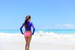 Setzen Sie die Frau im rashguard lebend ein aktiver Lebensstil auf den Strand Lizenzfreies Stockbild