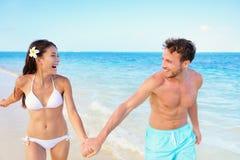 Setzen Sie die Paare auf den Strand, die den Spaß haben, der auf Strandferien glücklich ist Stockbilder