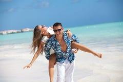 Setzen Sie die Paare auf den Strand, die den Spaß haben, der an den karibischen Feiertagen lacht Lizenzfreie Stockfotos