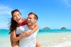 Setzen Sie die Paare auf den Strand, die den Spaß haben, der an Hawaii-Feiertag lacht Stockbild