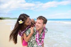 Setzen Sie die Paare auf den Strand, die den Spaß haben, der an Hawaii-Feiertag lacht Lizenzfreie Stockbilder