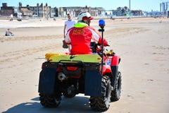 Setzen Sie die Patrouille auf einer vierrädrigen Droschke den Strand aufpassend auf den Strand stockbild