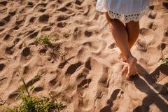Setzen Sie die Reisefrau auf den strand, die auf sandige verlassende Abdrücke im Sand geht Schließen Sie herauf Detail von weibli Lizenzfreies Stockfoto