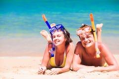 Setzen Sie die Reisepaare auf den strand, die das Spaßschnorcheln haben und auf Sommerstrandsand mit Schnorchelausrüstung liegen Lizenzfreie Stockfotos