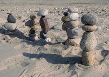 Setzen Sie die Steinzahlen auf den strand, die weg in den Abstand marschieren Stockbilder