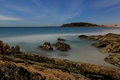 Setzen Sie durch Mondschein auf den Strand, wenn nebelhaftes Wasser über Felsen rollt lizenzfreies stockfoto