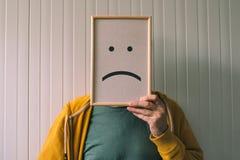Setzen Sie ein trauriges pessimisic Gesicht an, Traurigkeit und deprimierende Gefühle Co Stockbilder