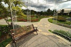 Setzen Sie in einem Garten mit den Blumen und Laube auf die Bank -, die nett sind und neeat outdoo Stockbilder