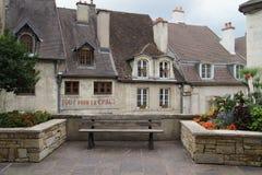 Setzen Sie an einem kleinen französischen Dorfplatz - alte Stadt auf die Bank Stockfotografie