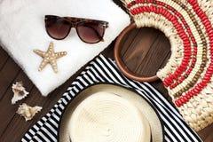 Setzen Sie Einzelteile mit Strohhut, Tuch und Sonnenbrille auf hölzernem Hintergrund auf den Strand Lizenzfreie Stockbilder
