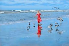 Setzen Sie Ferien auf den Strand Frau, die auf Strand durch Meer mit Seemöwen läuft lizenzfreies stockfoto
